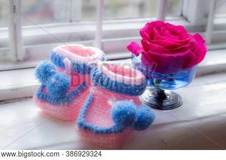 Pink Woven Childrens Shoes With Blue Knitted Edging Stand Against The Background Of A Window And A R