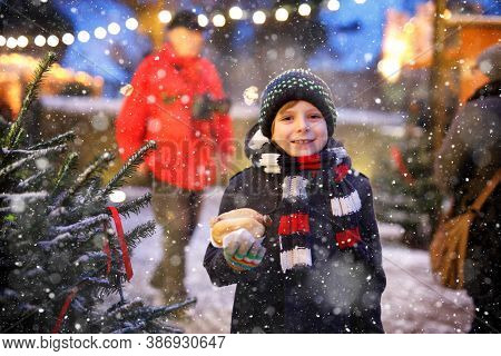 Little Cute Kid Boy Eating German Sausage And Drinking Hot Children Punch On Christmas Market. Happy