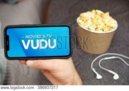 Vudu Movies And Tv Logo On The Mobile Phone Screen With Popcorn Box And Apple Earpods On The Backgro
