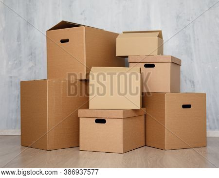 Moving Day Or Postal Delivery Concept - Brown Cardboard Boxes Stacked On The Floor Over Gray Wall Ba