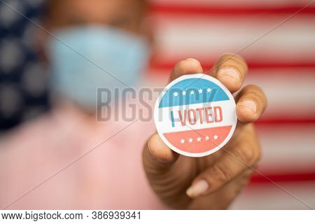 Close Up Shot Man In Medical Mask Showing I Voted Sticker And Putting On Shirt With Us Flag As Backg