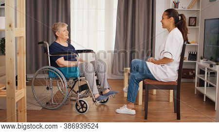 Senior Woman In Wheelchair Having A Conversation With Nurse. Old Person Retirement Home, Healthcare