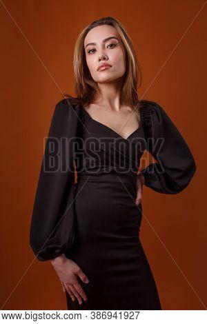 Charming Elegant Fashion Model Wearing Black Dress With Deep Neckline Posing On Orange Background. A