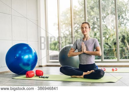 Portrait Of Sport Woman In Sportswear Sitting Relax And Practicing Yoga  Fitness Exercise With Blue