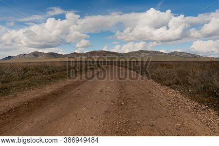 Landscape With A Wide Dirt Road Going Through The Steppe Up To The Hills. Dirt Country Road In Khaka