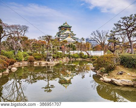 The Main Keep Of Osaka Castle, Osaka, Japan, Reflected In A Pool In The Grounds.