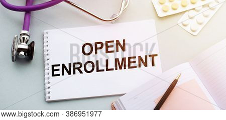 Open Enrollment Text Written In A Notebook Lying On A Medicine Desk And A Stethoscope. Medical Conce