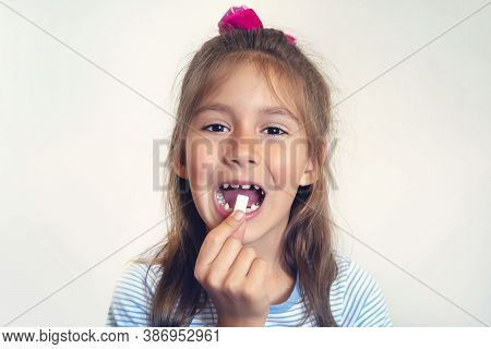 Girl Puts White Gum Shaped Pads In Her Open Mouth. Cleaning Your Teeth With Chewing Gum. Bad Habit,