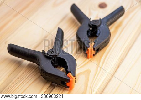 Two Plastic Spring Clamp On Wooden Background. Clamping Equipment. Woodworking Hand Tool.