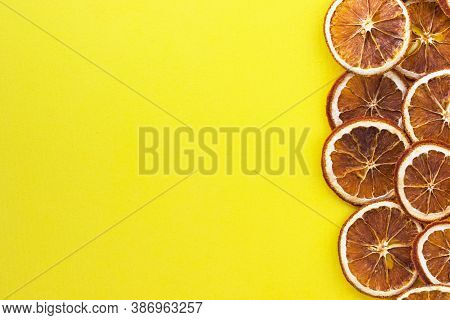 Slices Of Dried Orange On Yellow Background. Sweet Citrus Fruit. Homemade Christmas Natural Decorati