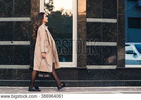Fashionable Woman With Long Hair Walking In The City. Woman Wears Trendy Coat And Shoes. Street Fash