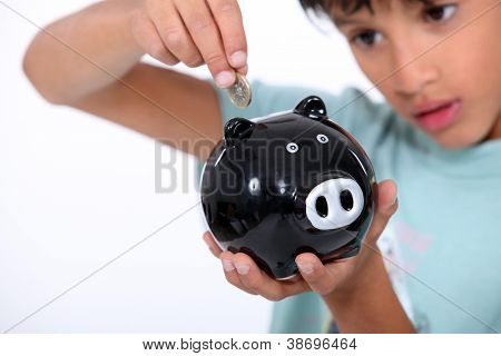 boy putting a coin into a money box