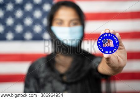 Selective Focus On Hands, Girl With Hijab Or Head Covering And Mask Worn Showing I Voted Sticker Wit