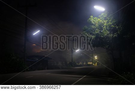 Empty Road Underneath Street Light With Smoke At Night And Ufo On Background