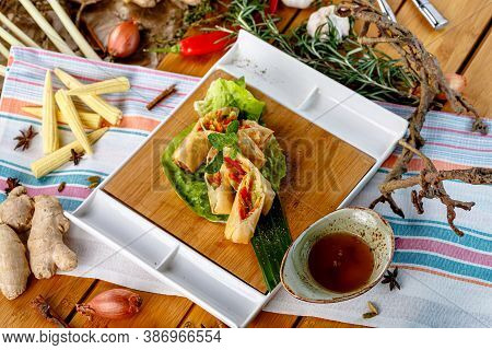 Spring Rolls With Vegetables And Sauce Are On The Plate