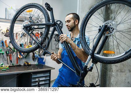 Bicycle repair in workshop, man checks mechanisms