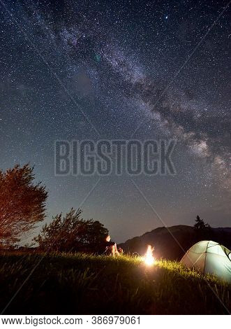 Vertical Shot. Night Camping In The Mountains. Male Tourist Enjoying Starry Sky With Milky Way, Havi