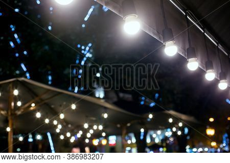 Textile Umbrella With Wooden Frame And String Lights Glowing With White Light On Backyard Terrace, C