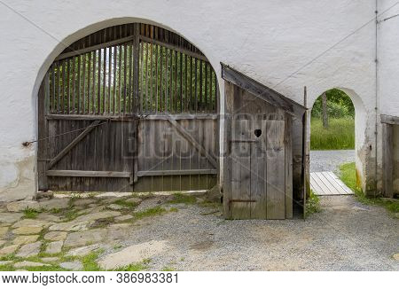 Historic Entrance And Gate With Wooden Pit Latrine In Between