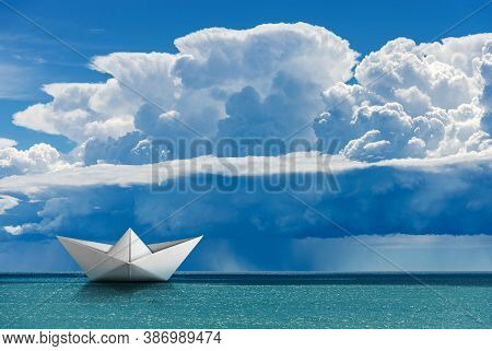 White Paper Boat In The Turquoise Sea Under The Sky With Cumulonimbus And Torrential Rain.