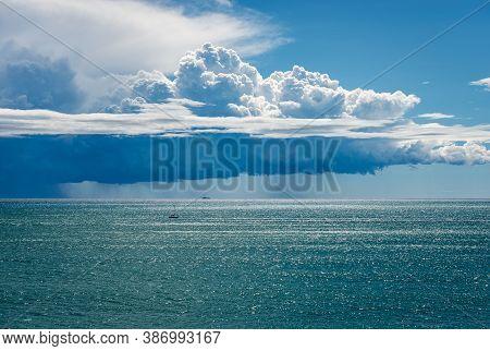 Cumulus Clouds (cumulonimbus) With Torrential Rain On The Horizon Over The Mediterranean Sea. Gulf O