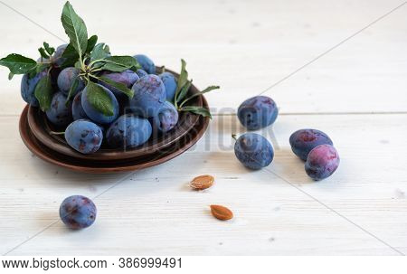 A Few Ripe Blue Plums In A Brown Plate On A White Wooden Table. Several Bones Lie Separately