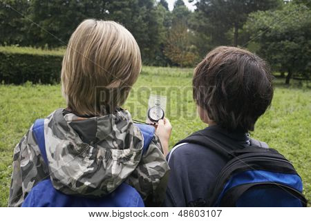 Rear view of two young boys with backpacks using compass