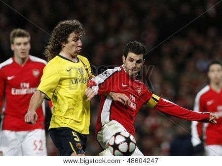 LONDON, ENGLAND. 31/03/2010. Barcelona's Carles Puyol fouls Arsenal'sCesc Fa?bregas to concede a penalty during the  UEFA Champions League quarter-final at the Emirates Stadium