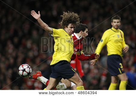 LONDON, ENGLAND. 31/03/2010. Barcelona player Carles Puyol fouls Arsenal player Cesc Fa?bregas (captain) and concedes a penalty  during the  UEFA Champions League quarter-final at the Emirates Stadium