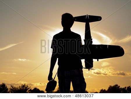 Silhouette of a young man with a model rc airplane and a controller, against sunset sky