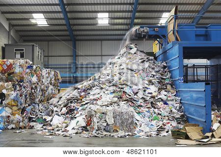 Waste falling on pile from conveyor belt at recycling factory