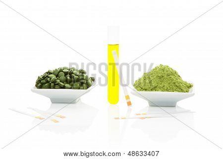 Muestra de orina, tiras reactivas de Ph y pastillas verdes.