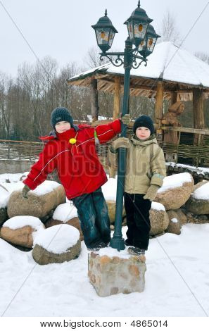 Two Boys Play Outdoor In Winter Near A Lantern