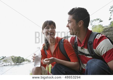 Cheerful young woman holding waterbottle by a man outdoors