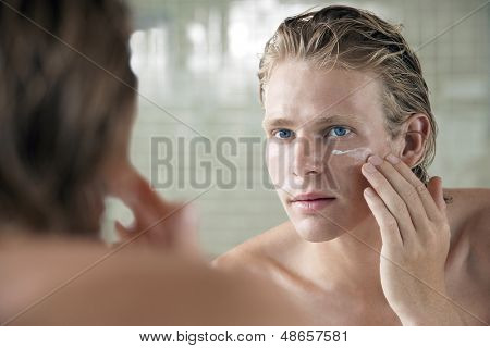 Closeup of handsome young man applying facial cream in front of mirror