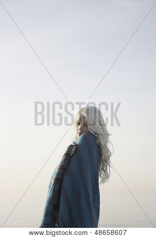 Side view of beautiful blond woman wrapped in blanket standing against clear sky