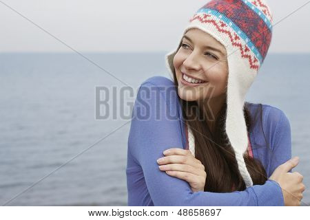 Happy young woman wearing knit hat looking away while standing against sea at beach