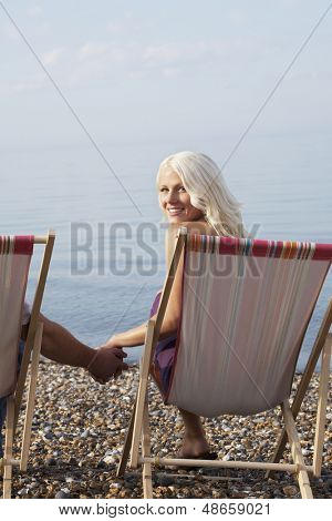 Portrait of beautiful woman holding man's hand while sitting on deckchair at beach