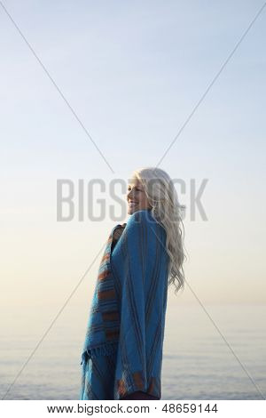 Side view of beautiful happy woman wrapped in blanket standing against clear sky on beach