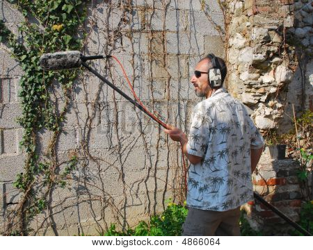 A sound engineer at work during on location in Italy using a shotgun microphone with a wind protection shield poster