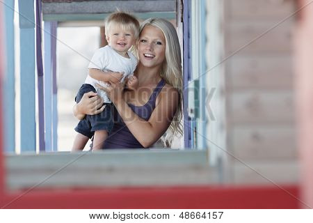 Portrait of attractive young woman carrying baby boy at porch