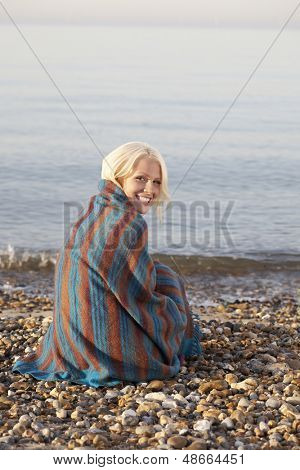 Portrait of beautiful young woman wrapped in blanket sitting at beach