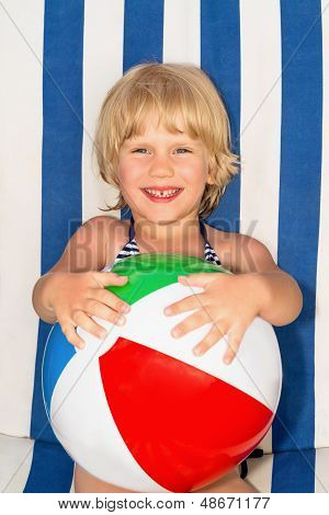 Happy Little Girl With A Ball On A Lounger On The Beach
