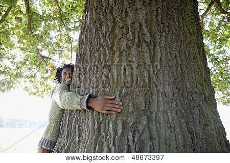 Happy young African American man hugging tree trunk at park