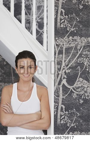 Portrait of beautiful young woman with arms crossed leaning on door frame at home