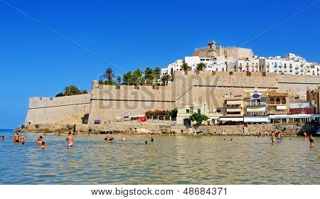 PENISCOLA, SPAIN - JULY, 26: Bathers in North Beach, facing the castle, on July 26, 2013 in Peniscola, Spain. The town is a typical summer destination in the North of the Valencian Community
