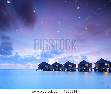 Starry skies over water villa cottages on island of Kuredu, Maldives, Lhaviyani atoll, shot with a tilt and shift lens
