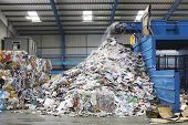 Waste falling on pile from conveyor belt at recycling factory poster