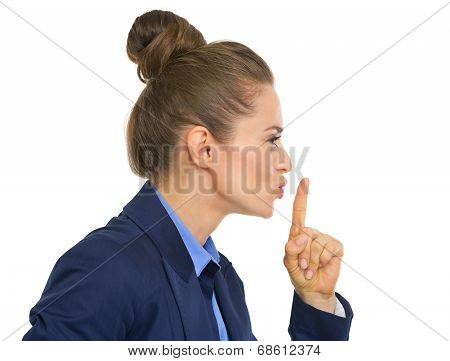 Profile portrait of business woman showing shh gesture poster