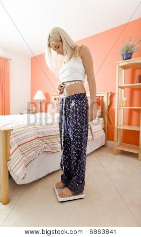 Woman Measuring Waist And Using Scale In Bedroom